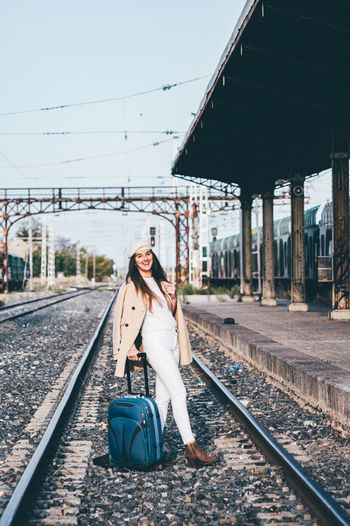 Full length portrait of young woman at railroad station