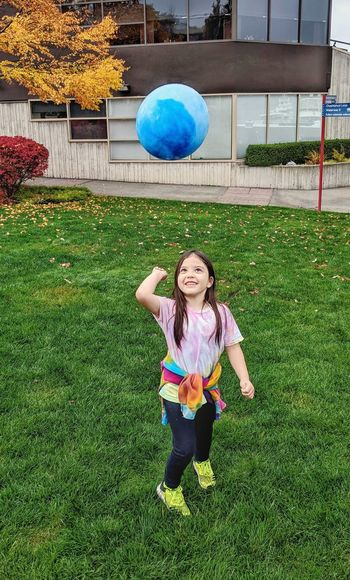 Full length of a smiling girl playing with ball