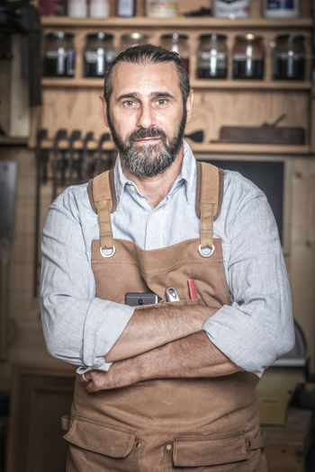 Portrait Of Carpenter Standing In Workshop