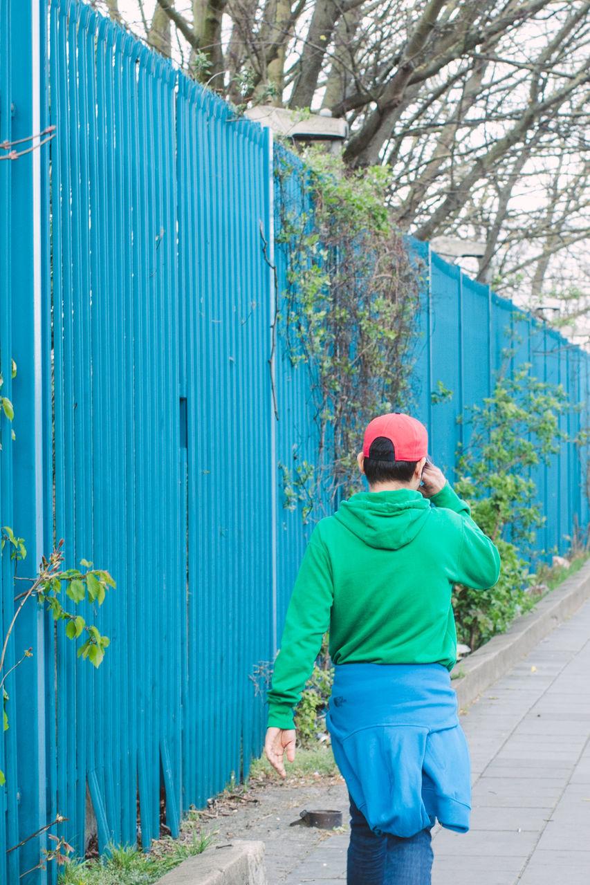 Rear View Of Boy Walking On Sidewalk