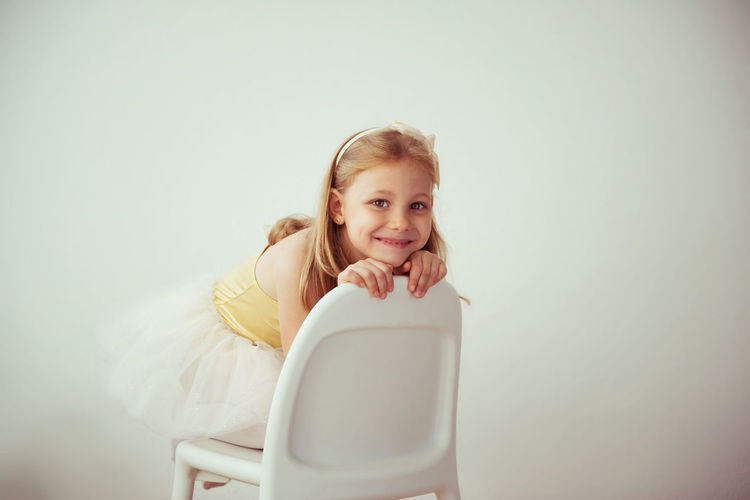 Portrait of cute smiling girl sitting on chair against wall
