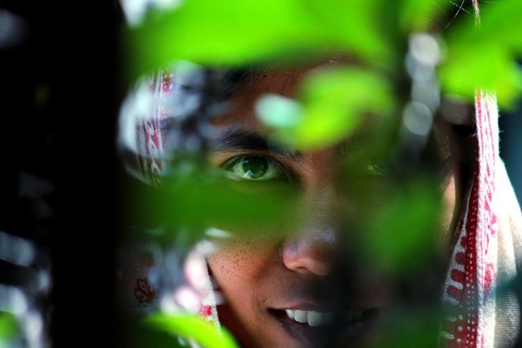 Close-up of woman seen through plant
