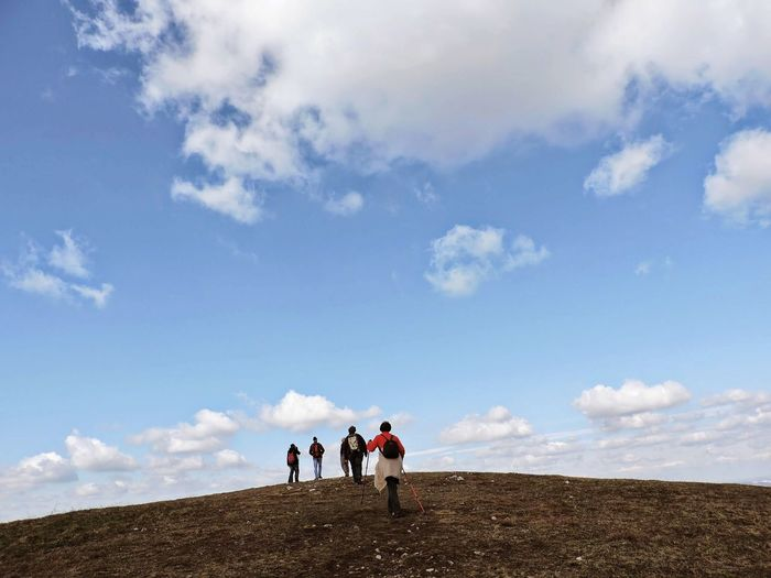 Low angle view of friends hiking on mountain against blue sky