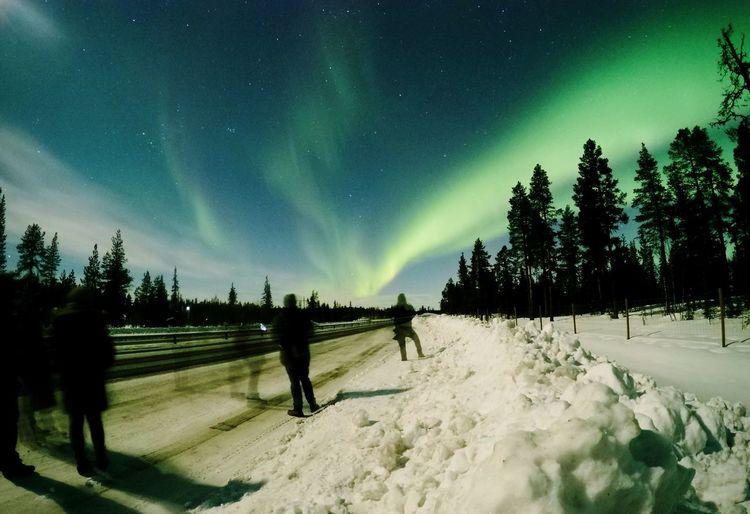 Blurred motion people on snow covered road against aurora borealis