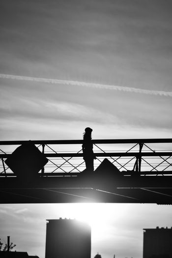 Silhouette man standing on bridge against sky