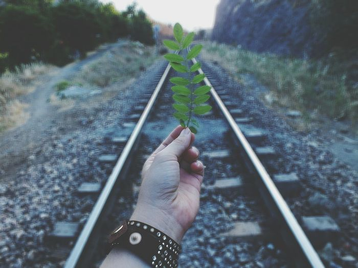 Close-up of hand holding twig over railroad track