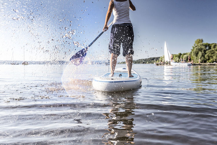 Low section of man paddleboarding on sea