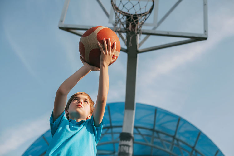 Low angle view of boy playing basketball against sky