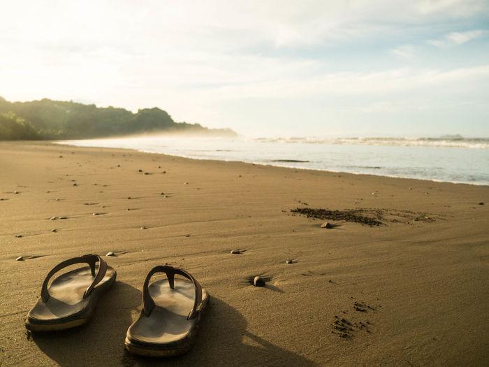 Flip-flops at beach against sky