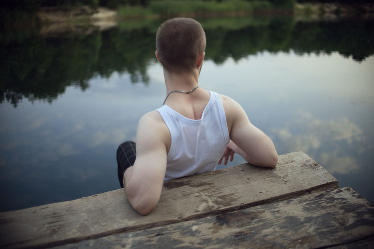 Rear view of man sitting on lake against trees