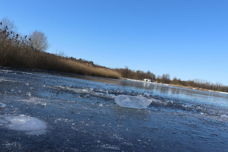 Scenic view of frozen landscape against clear blue sky