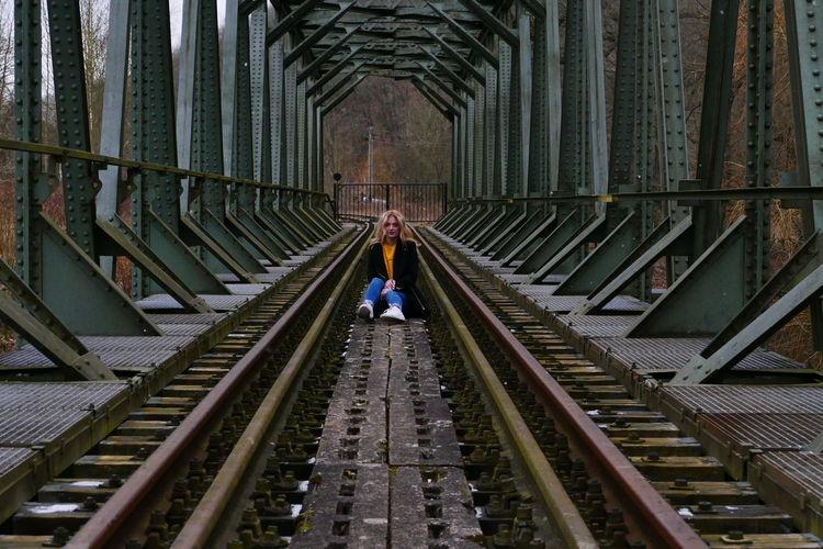 Woman Sitting On Railway Bridge