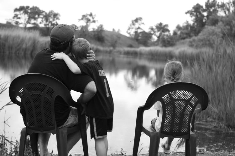 Father with two children sitting on riverbank