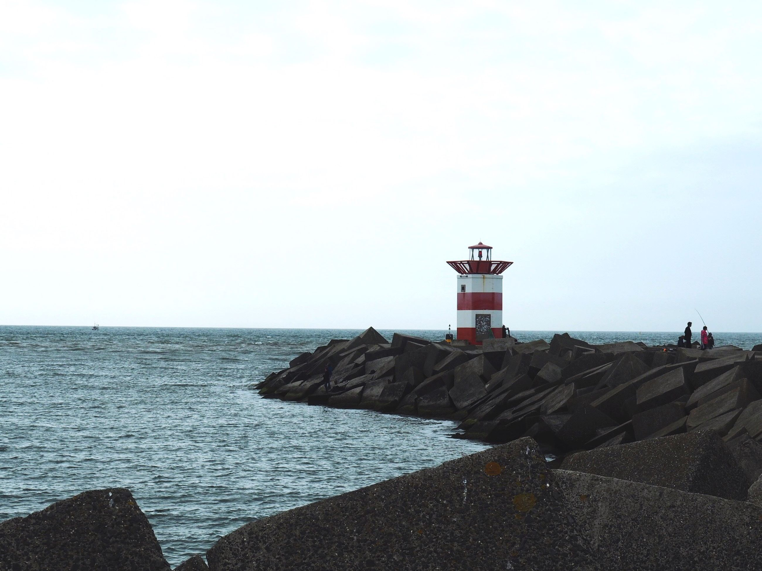 sea, horizon over water, water, direction, lighthouse, tranquil scene, rock - object, tourism, tranquility, scenics, rock formation, travel destinations, sky, nature, beauty in nature, shore, outdoors, cliff, person, non-urban scene, day
