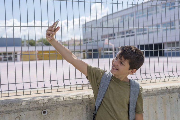Student making a selfie outdoors, next to school fence Back To School Backpack Boys Casual Clothing Caucasian Cheerful Childhood Day Elementary Age Fence Leisure Activity Lifestyles Male One Person Outdoors Outside People Real People School School Life  Selfie Smart Phone Standing Teenager Young Adult
