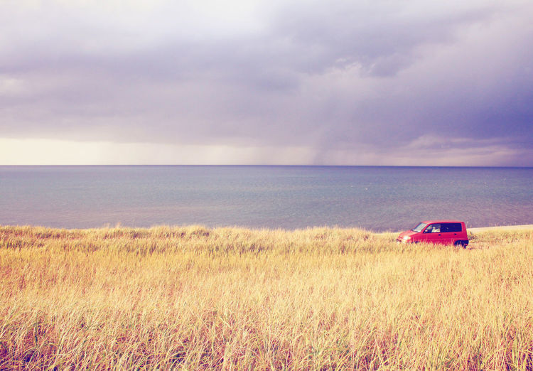 Sky Horizon Land Mode Of Transportation Transportation Cloud - Sky Scenics - Nature Plant Grass Horizon Over Water Sea Landscape Field Environment Land Vehicle Day No People Water Rural Scene Outdoors Car Field Red Car Nature