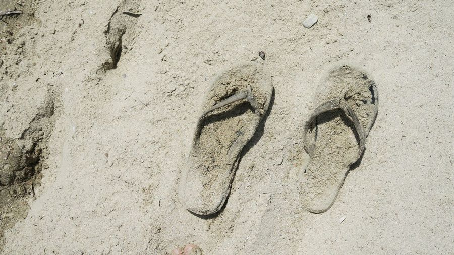 pair of flip flops covered with sand Sandy Beach Vacation Shoe Footwear Flipflop Flip Flops Beach Sand Full Frame High Angle View FootPrint Close-up