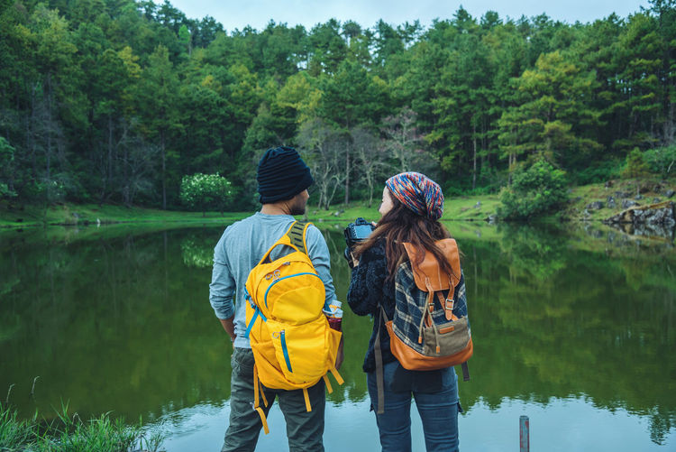 Rear view of couple standing by lake at forest