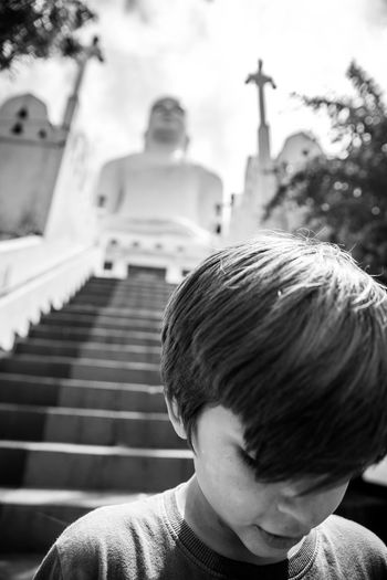 Boy on staircase against temple and sky