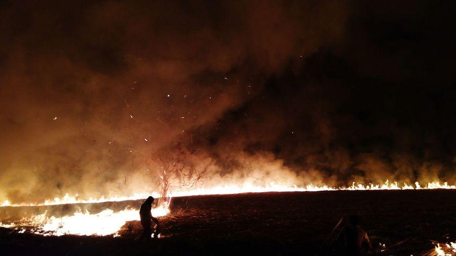 Man sitting on burning field at night