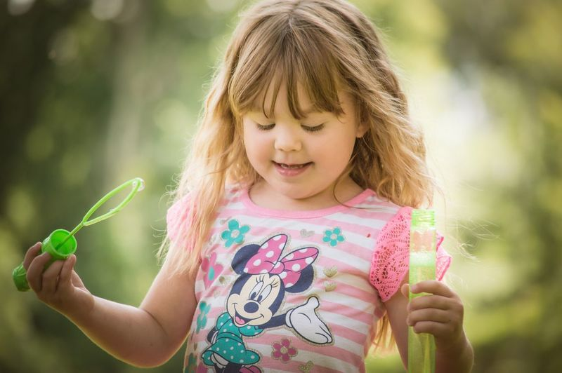 Close-up of girl holding pink while standing against plants