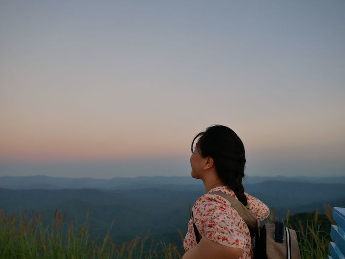 Woman looking at mountains against sky during sunset