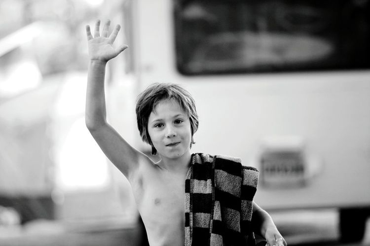 Portrait of young boy waving