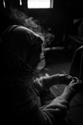 Side view of person wearing oxygen mask sitting in darkroom