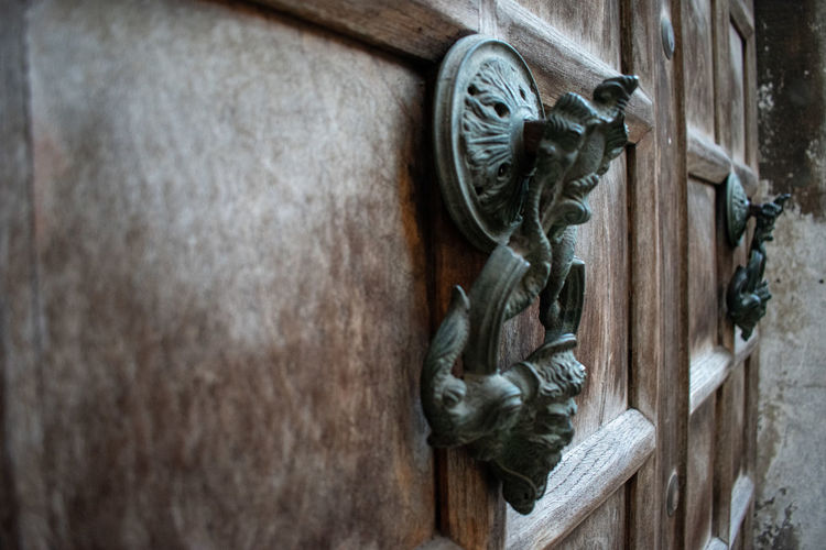 Art And Craft No People Wood - Material Metal Close-up Door Knocker Sculpture Door Entrance Old Knob Day Representation Creativity Animal Representation Design Selective Focus Wall - Building Feature Outdoors