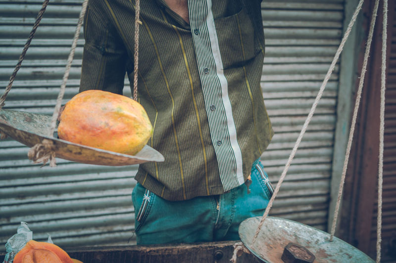 Midsection of man holding papaya on weight scale at market