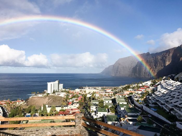 Water Sky Beauty In Nature Rainbow Sea Scenics - Nature Cloud - Sky Nature Day Architecture Building Exterior Sunlight Idyllic Beach Land Built Structure City Horizon Over Water Double Rainbow No People