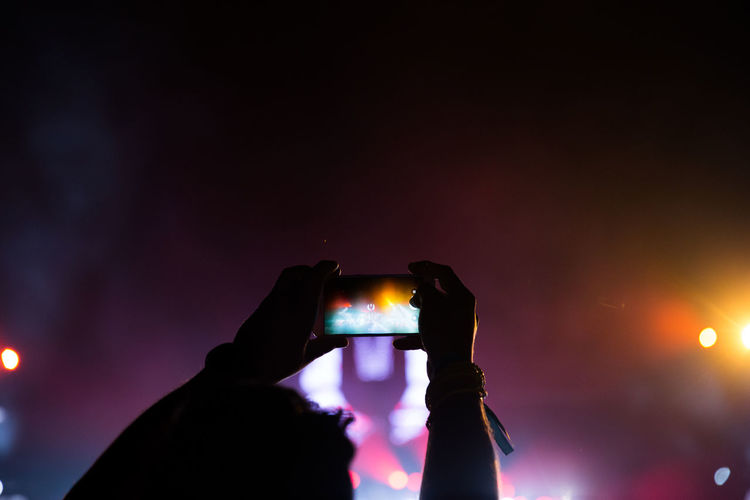 High Section Of Man Photographing Concert At Night