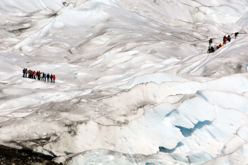 Two groups of tourists on a snow covered spectacular mountain