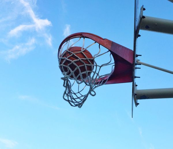 Low angle view of basketball in hoop against sky