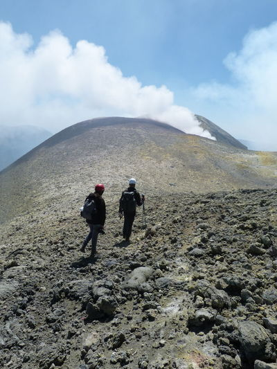 On the edge of Etna crater, sulfur cloudTwo People Hiking Mountain Cloud - Sky Volcanic Crater Togetherness People Outdoors Day Adults Only Men Full Length Adventure Sky Only Men Adult Landscape Nature Climbing Etna Etna Volcano Volcano Volcanic Landscape presso Catania Lost In The Landscape