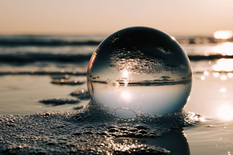 Close-up of crystal ball on beach against sky during sunset