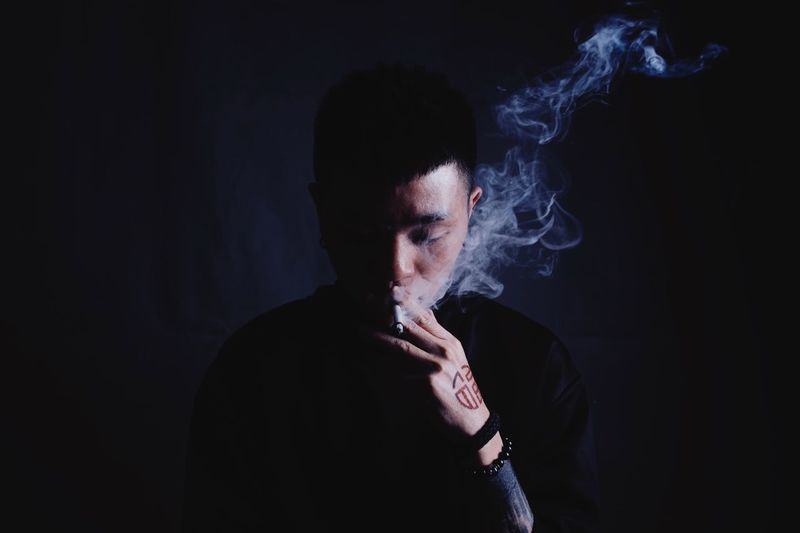 Close-Up Of Man Smoking Cigarette Against Black Background