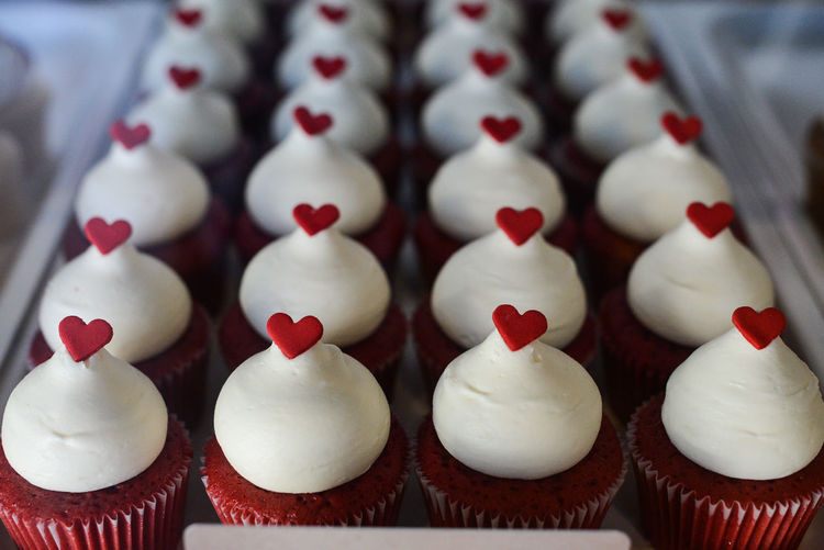 High angle view of cupcakes with whipped cream and heart shape candies