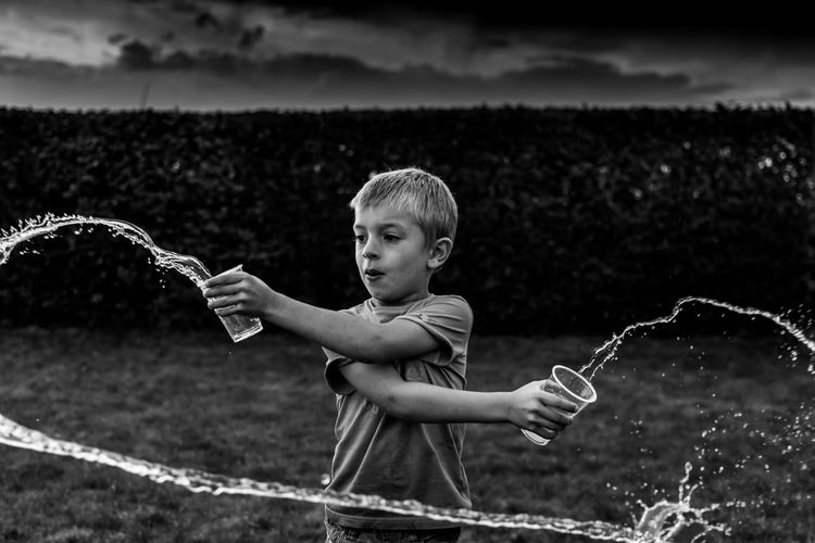 Boy throwing water on land