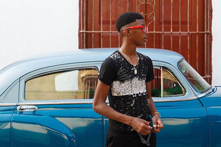 Boy standing by car