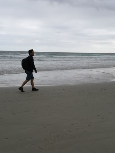 Full length of man walking at beach against sky