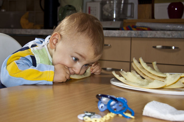 Baby boy eating fruit at table