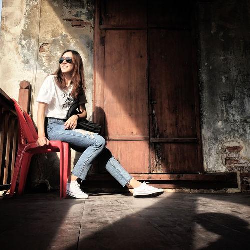 Full length portrait of woman sitting on door