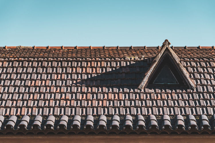 Low angle view of roof and building against clear sky