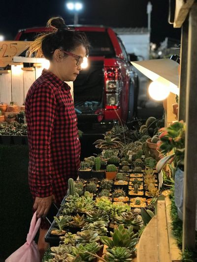 Side View Of Woman Looking At Succulent Plants For Sale In Market Stall