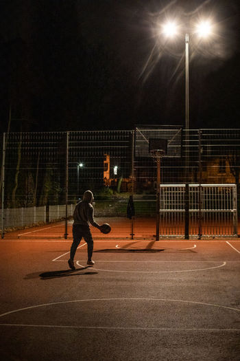 Man playing with ball on field at night