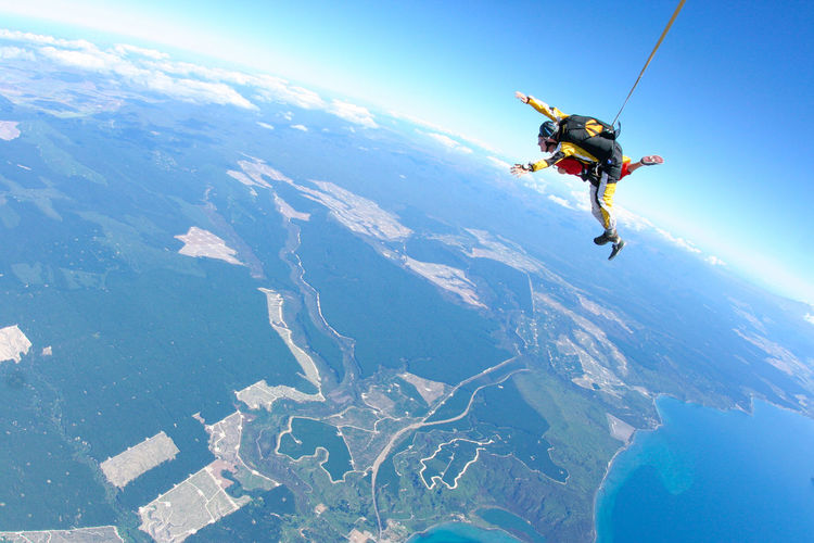 People skydiving over landscape