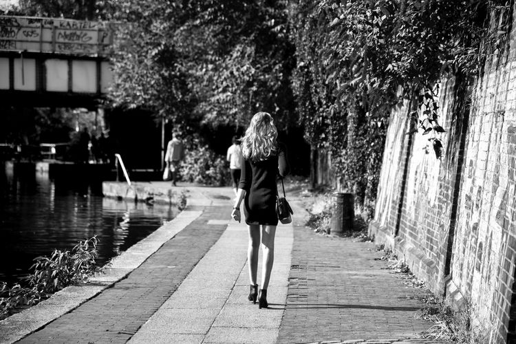 Rear view of woman walking on footpath by canal