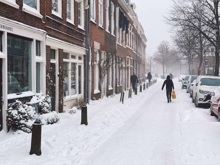 People walking on street amidst buildings during winter