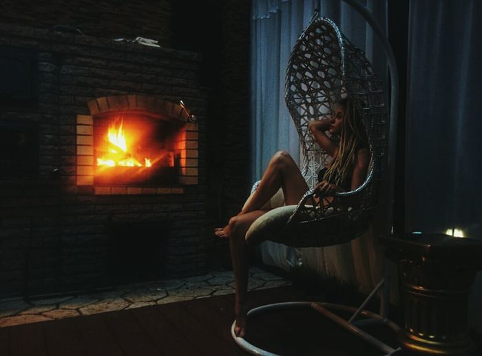 Full length of sensuous woman sitting in swing by fireplace at home